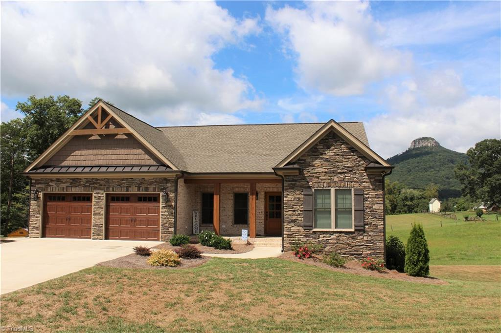 Stunning brick home with picturesque views, built to the nines! Only lived in 1 yr. You will not find any nicer kitchen, Granite counters, high definition tile back splash, custom cabinets, custom lighting, and Kitchen aid appliances. The home boasts, remote shade on porch, trex decking, stamped concrete, hickory flooring throughout, Low e windows, Superior wall basement, Tiled showers and floors in bathrooms, 50 yr shingle roof, screen porch and 40 x 30 rv shelter, studded out unfinished basement also.
