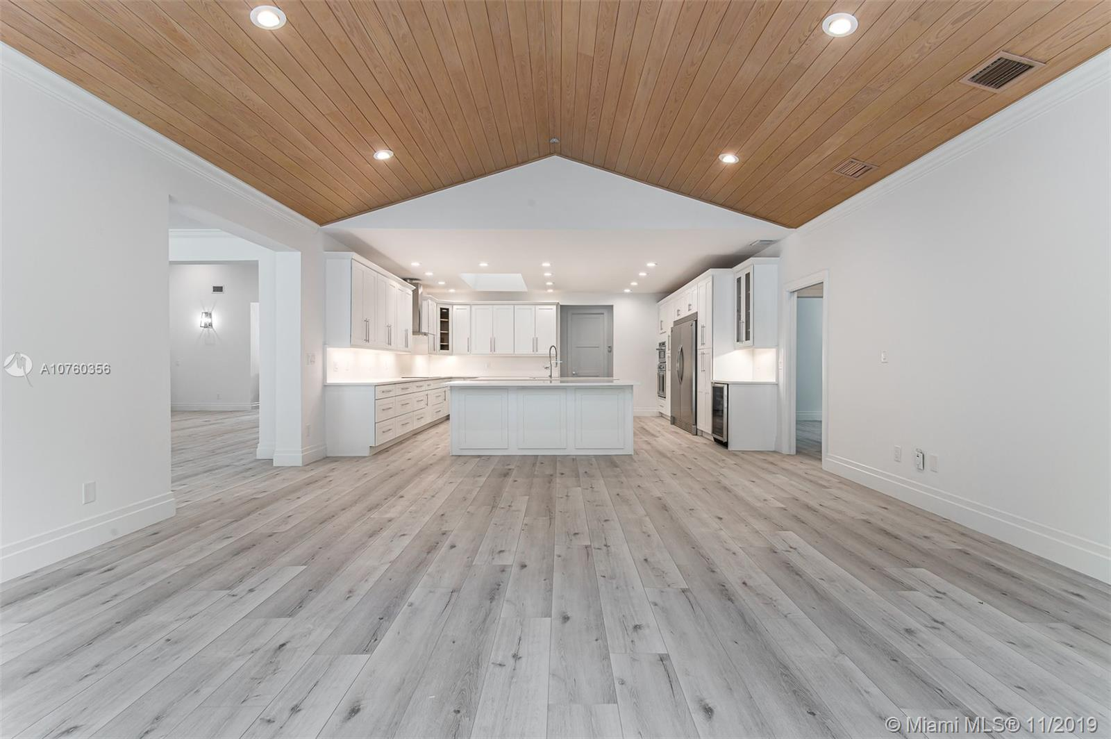 Brand New XXL open chef's kitchen featuring Top of the Line SS appliances, chrome finishes, custom wood shaker cabinets, quartz countertops and back splash, endless seating and storage! Open Floor plan - adjacent to the XXL Family Room & Overlooking the scenic Pool/backyard!